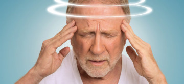 Headshot senior man with vertigo. Elderly male patient suffering from dizziness isolated on light blue background