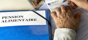 Dossier de pension alimentaire, paiement de la pension, redaction d'un cheque bancaire  Cadre photo representant le jeune garcon concerne par la pension alimentaire
